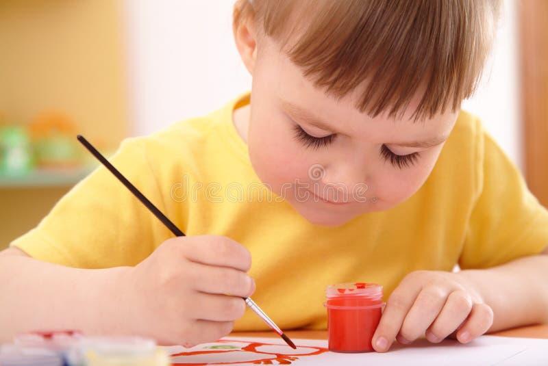 L'enfant dessine avec des peintures dans l'école maternelle photos stock