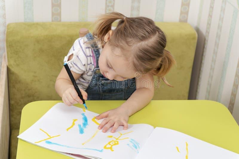 L'enfant dessine avec la concentration photo libre de droits