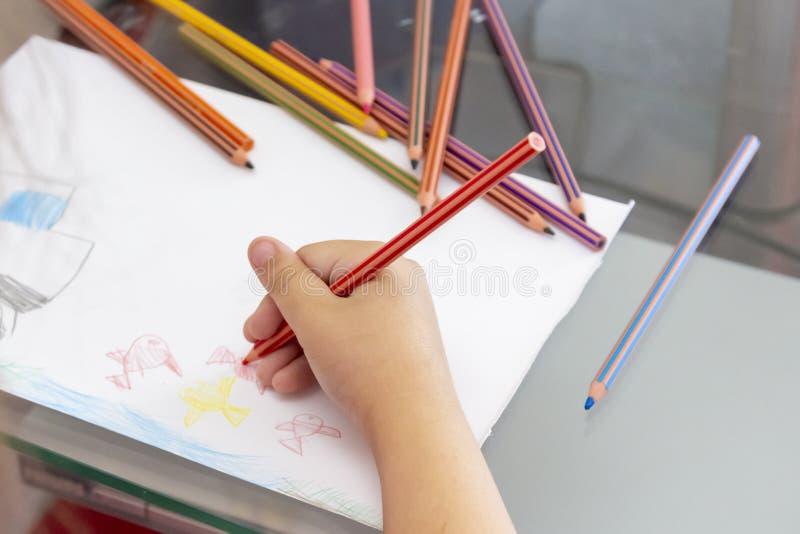 L'enfant dessine avec les crayons colorés Le dessin des enfants sur le thème de la pêche avec le poisson rouge, voiture photos stock