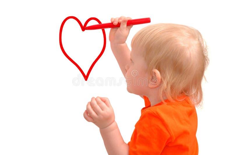 L'enfant dessine le crayon rouge un coeur photographie stock