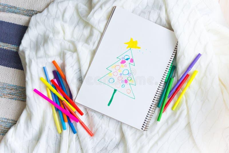 L'enfant dessine un arbre de Noël avec les crayons et le marqueur colorés photo libre de droits