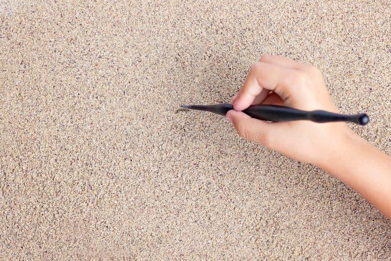 L'enfant dessine un bâton sur la mer avec le soleil Dessin du ` s d'enfants photos stock