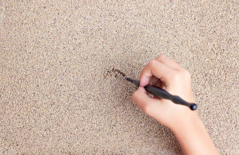 L'enfant dessine un bâton sur la mer avec le soleil Dessin du ` s d'enfants images stock