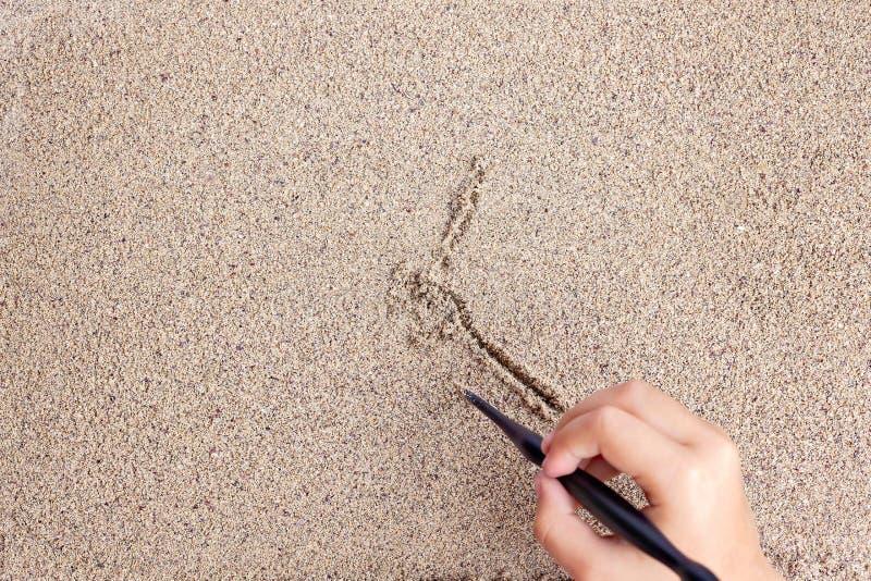 L'enfant dessine un bâton sur la mer avec le soleil Dessin du ` s d'enfants photographie stock