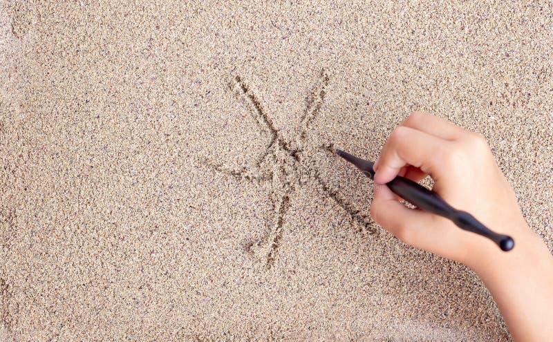 L'enfant dessine un bâton sur la mer avec le soleil Dessin du ` s d'enfants photo stock