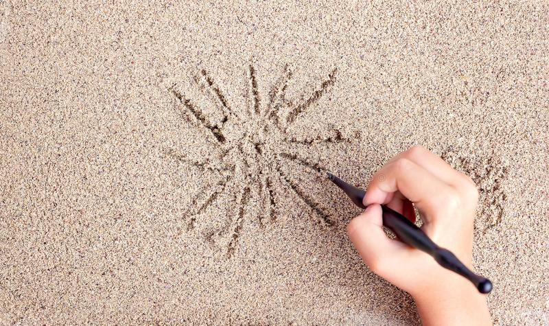 L'enfant dessine un bâton sur la mer avec le soleil Dessin du ` s d'enfants image libre de droits