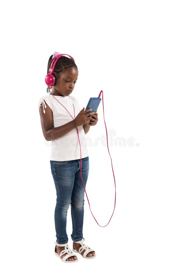 L'enfant en bas âge écoute la musique D'isolement sur le fond blanc photos stock