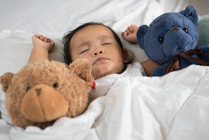 L'enfant en bas âge asiatique dormant avec le nounours concernent le lit, l'oreiller et la feuille blancs images stock
