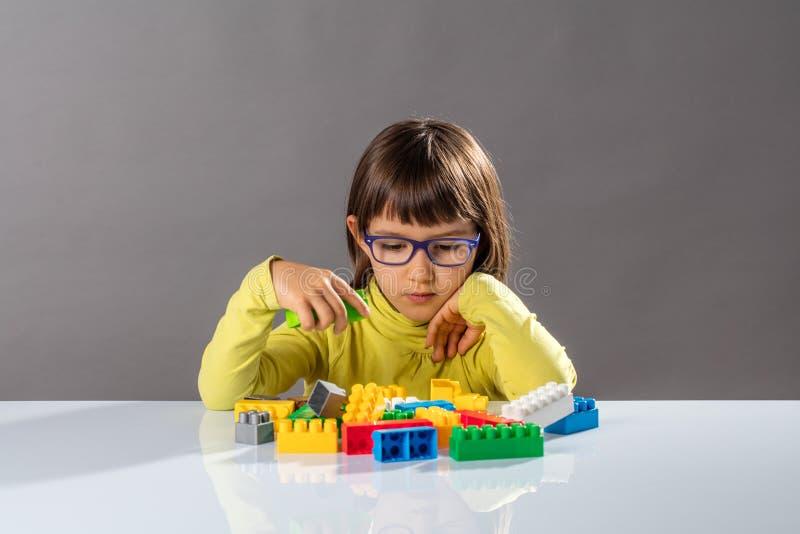L'enfant en bas âge avec des lunettes pensant à l'organisation joue avec l'imagination images stock