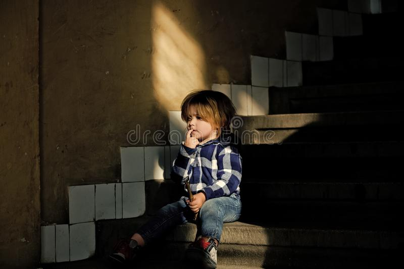 L'enfant en bas âge avec le visage de pensée s'asseyent sur des escaliers de maison images libres de droits