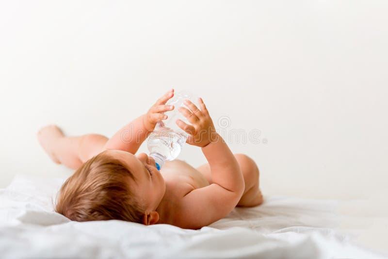 L'enfant en bas âge de bébé s'assied sur le lit blanc, sourires et les boissons arrosent de la bouteille en plastique Copiez l'es images stock