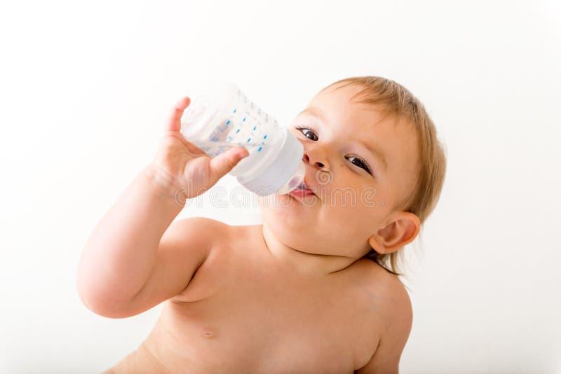 L'enfant en bas âge de bébé s'assied sur le lit blanc, sourires et les boissons arrosent de la bouteille en plastique Copiez l'es photographie stock