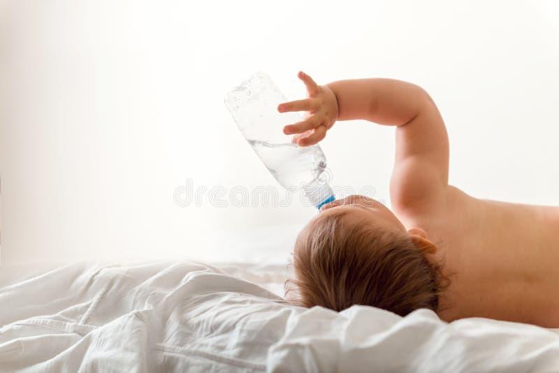 L'enfant en bas âge de bébé s'assied sur le lit blanc, sourires et les boissons arrosent de la bouteille en plastique Copiez l'es images libres de droits