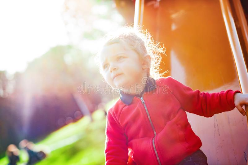 L'enfant en bas âge de fille joue sur la glissière au parc photos libres de droits