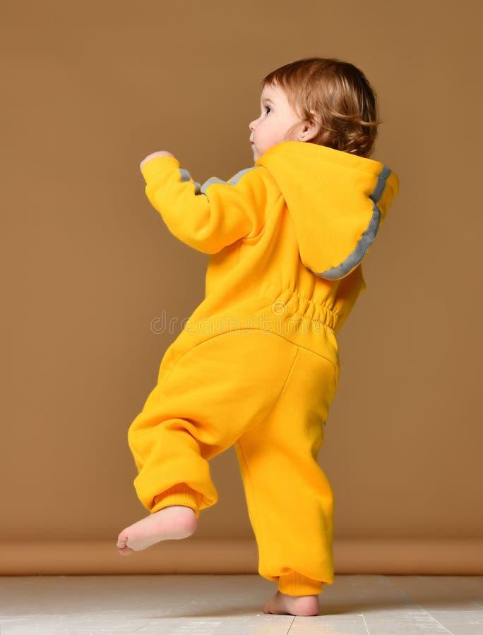 L'enfant en bas âge infantile d'enfant de bébé d'enfant dans des combinaisons jaunes d'hiver font des premières étapes sur le gri photos stock