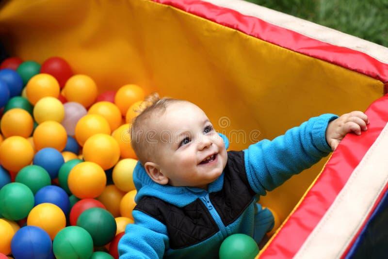 Enfant en bas âge dans la boîte de boules photo stock