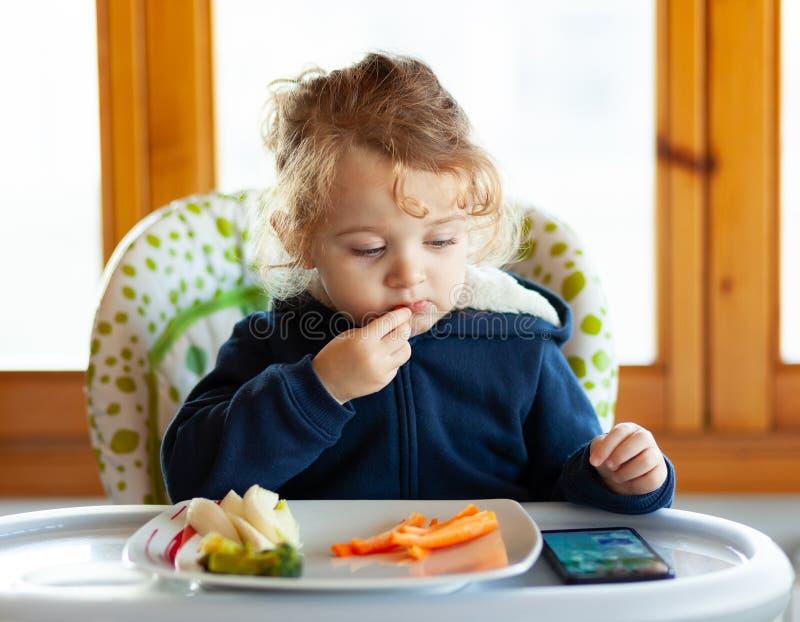 L'enfant en bas âge mange tout en observant des films au téléphone portable photographie stock libre de droits