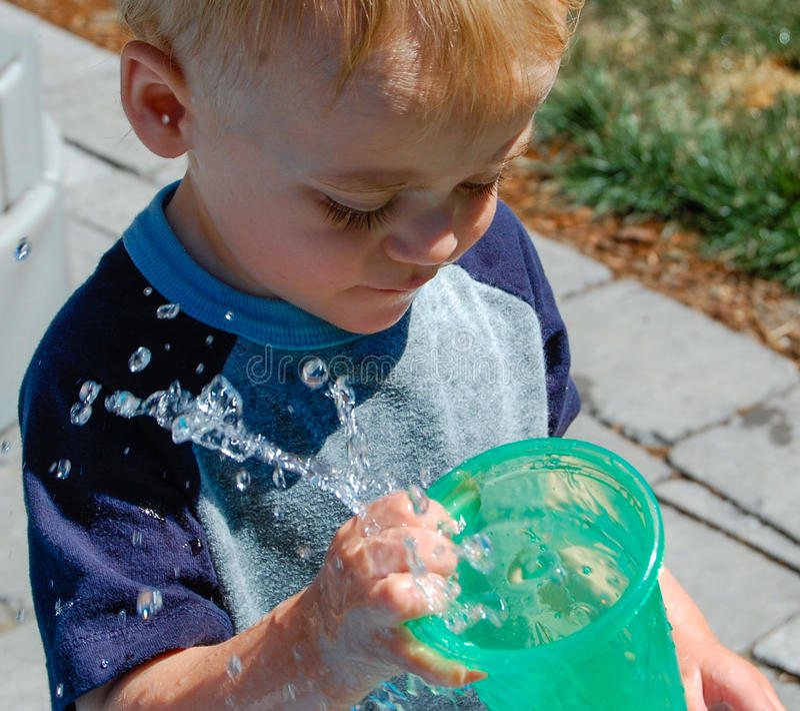L'enfant en bas âge renverse le verre d'eau de mouvement lent image libre de droits