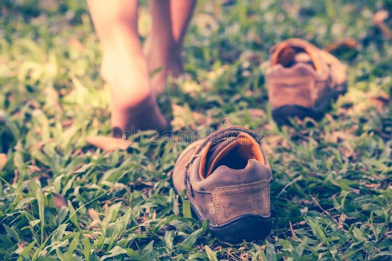 L'enfant enlèvent des chaussures Le pied de l'enfant apprend à marcher sur l'herbe image stock