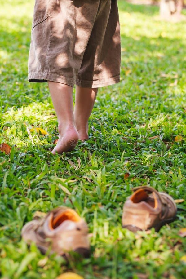 L'enfant enlèvent des chaussures Le pied de l'enfant apprend à marcher sur l'herbe images libres de droits