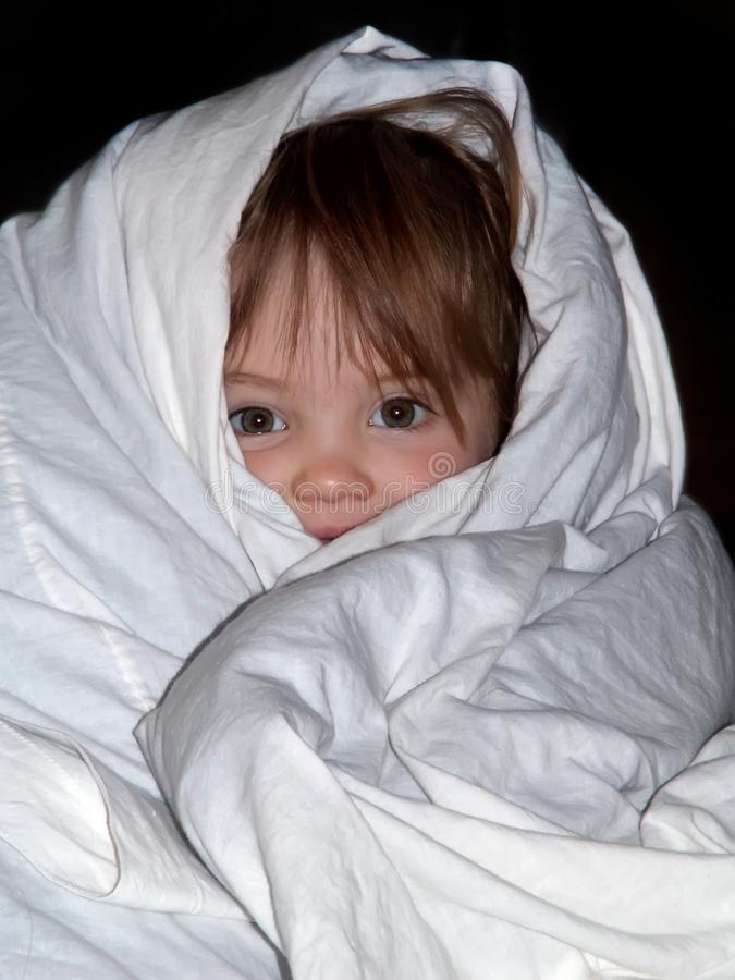 L'enfant est enveloppé dans la couverture image stock