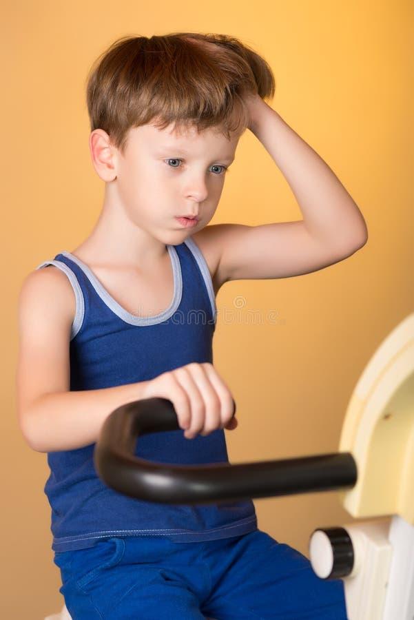 L'enfant est formé sur un vélo stationnaire Style de vie sain photos libres de droits