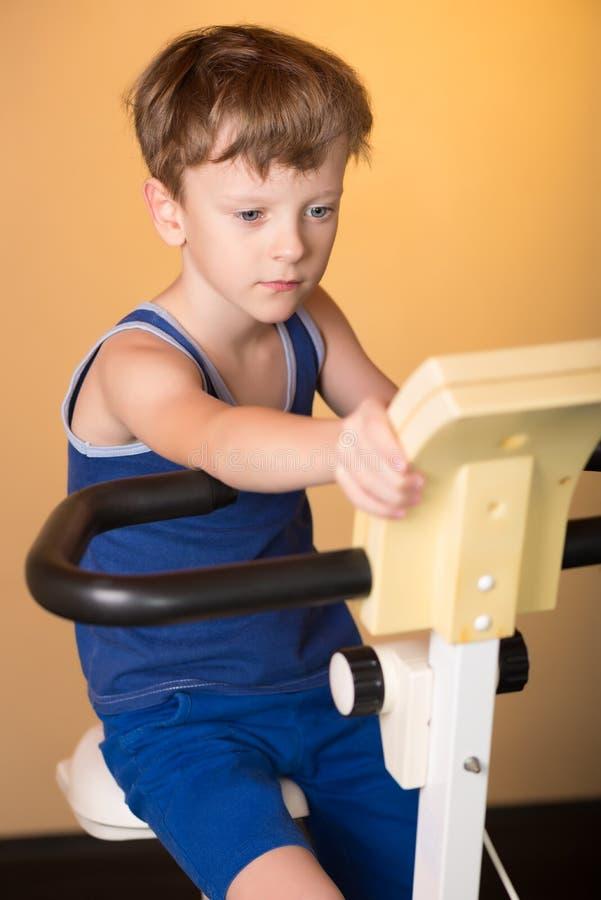 L'enfant est formé sur un vélo stationnaire Style de vie sain image libre de droits