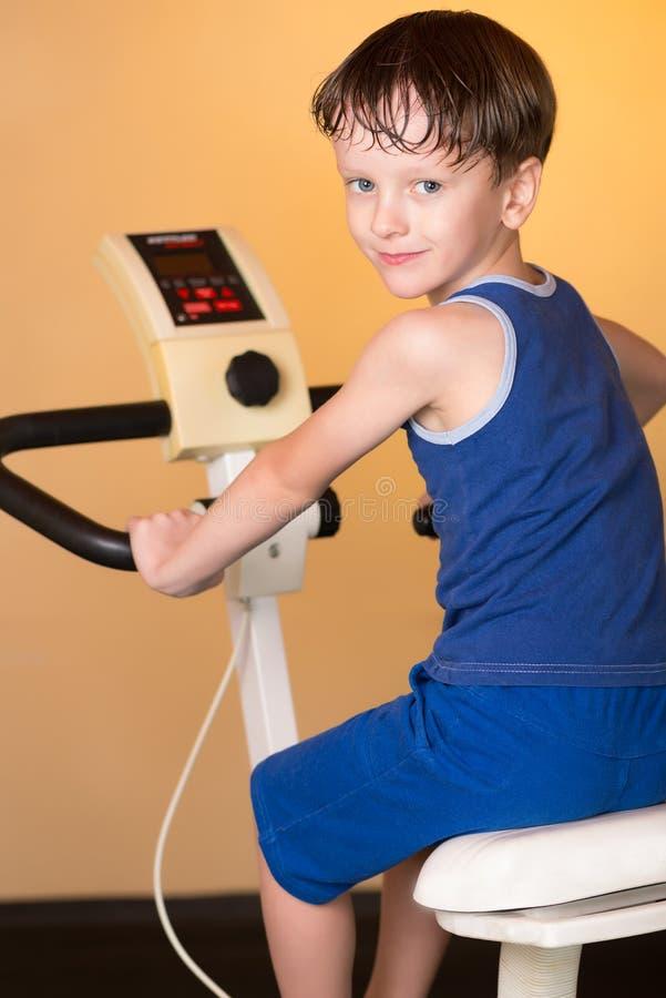 L'enfant est formé sur un vélo stationnaire Style de vie sain photo libre de droits