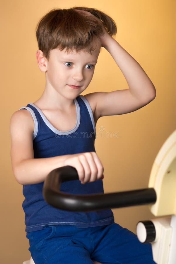 L'enfant est formé sur un vélo stationnaire Style de vie sain images stock