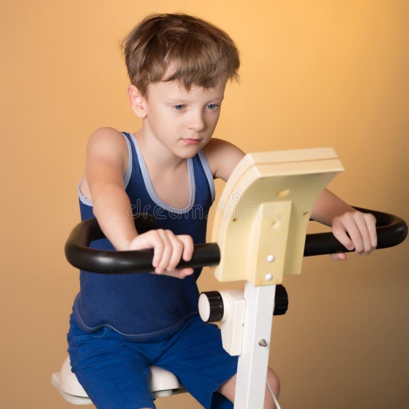 L'enfant est formé sur un vélo stationnaire Style de vie sain photographie stock