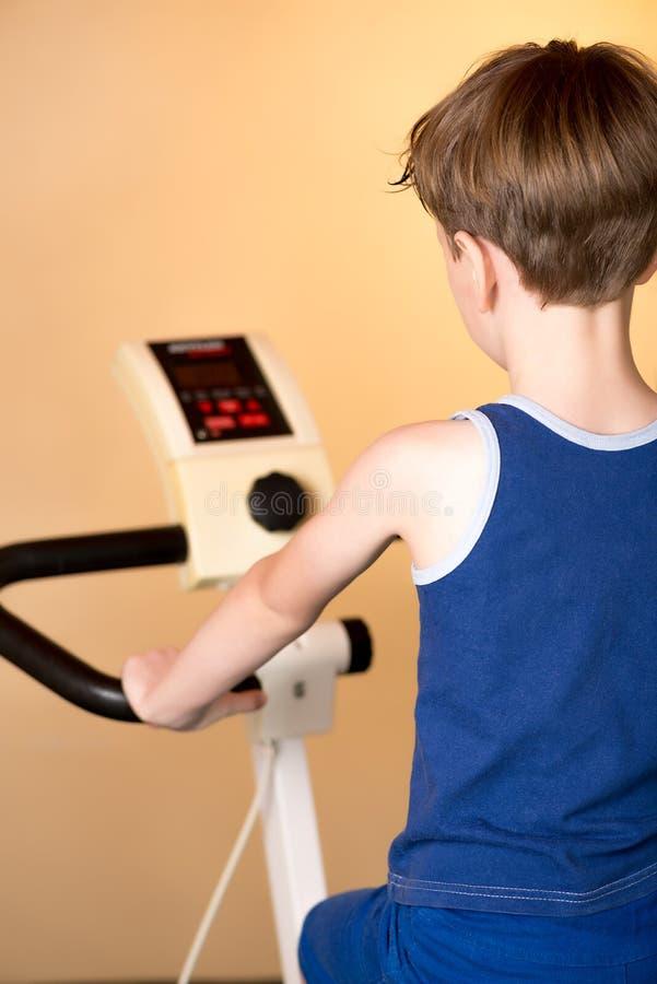 L'enfant est formé sur un vélo stationnaire Style de vie sain photos stock
