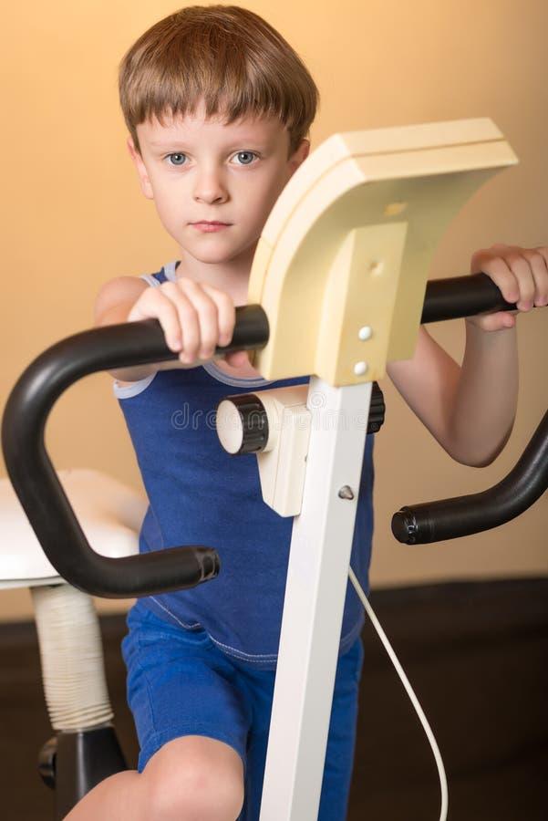 L'enfant est formé sur un vélo stationnaire Style de vie sain images libres de droits