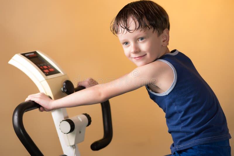 L'enfant est formé sur un vélo stationnaire Style de vie sain photographie stock libre de droits
