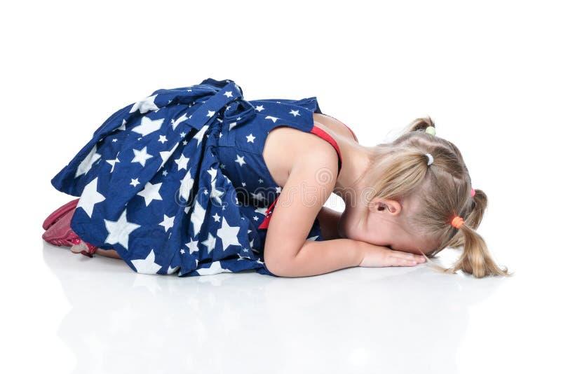 L'enfant est mensonge pleurant sur le plancher photos stock