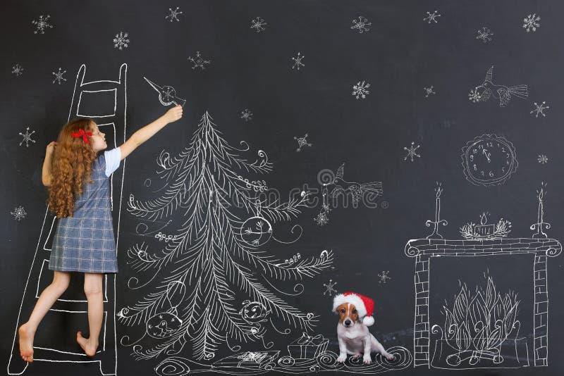 L'enfant et son chiot décore un dessin d'arbre de Noël sur le blackb photographie stock libre de droits