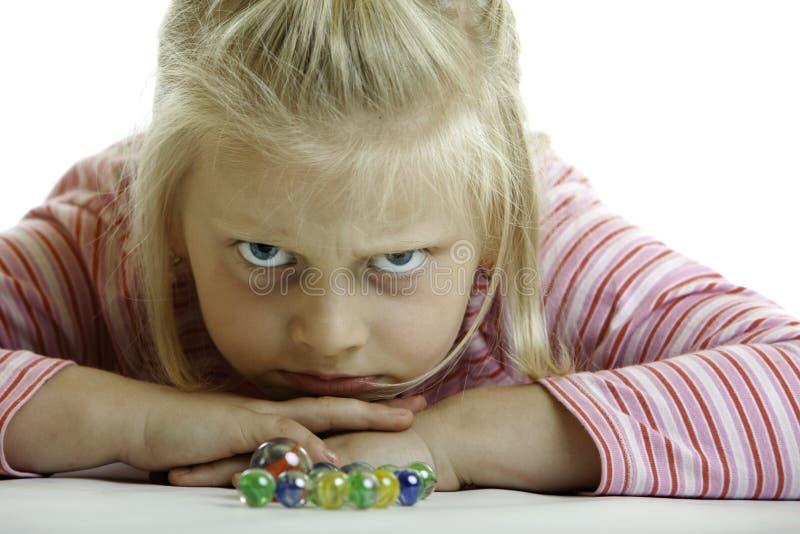 L'enfant fâché se trouve sur l'étage image stock
