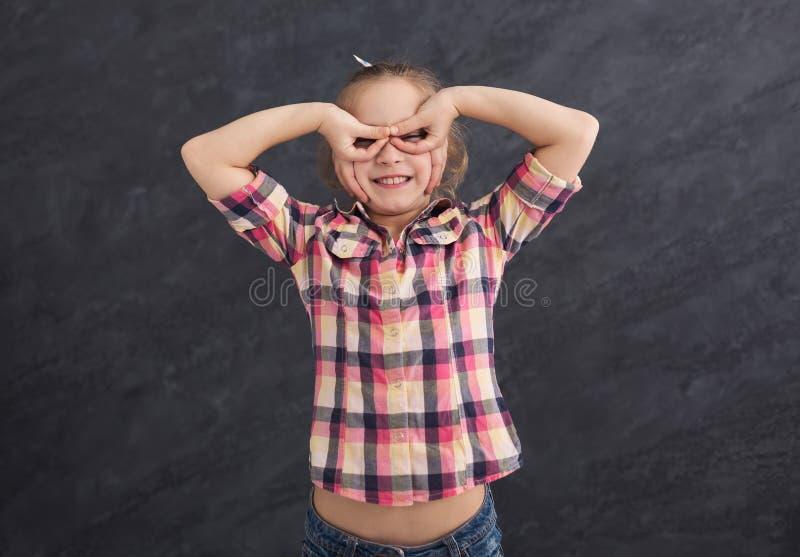 L'enfant féminin occasionnel tenant des doigts s'approchent des yeux comme des verres photographie stock