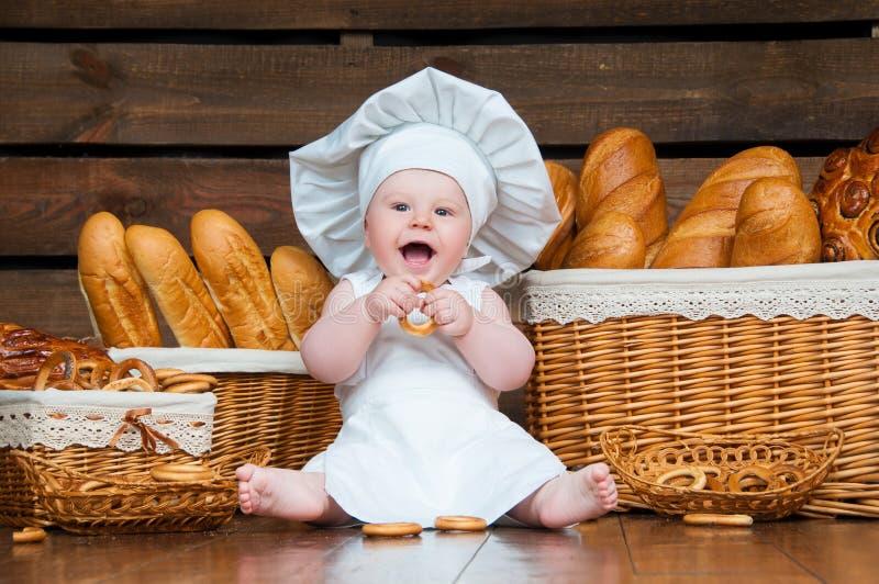 L'enfant fait cuire manger un bagel sur le fond des paniers avec les petits pains et le pain photos stock