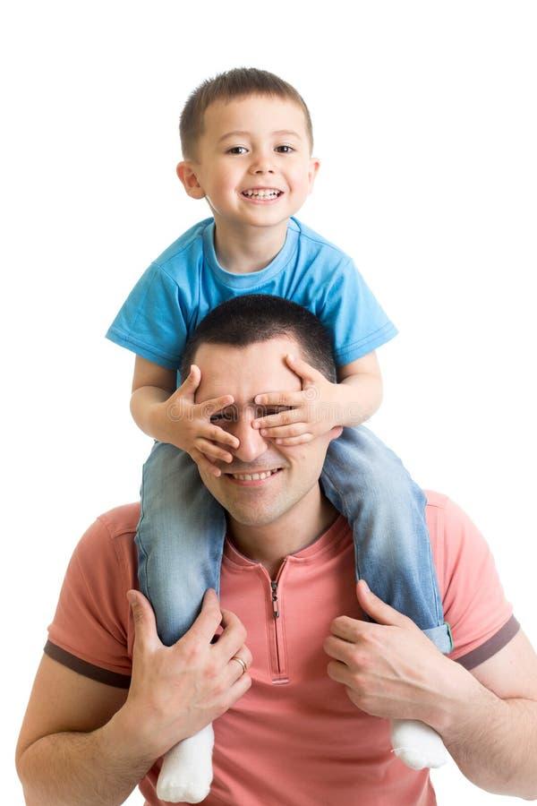 L'enfant ferme le père de yeux de mains Petit garçon heureux appréciant avec l'équitation sur le dos du ` s de père Verticale heu photo libre de droits