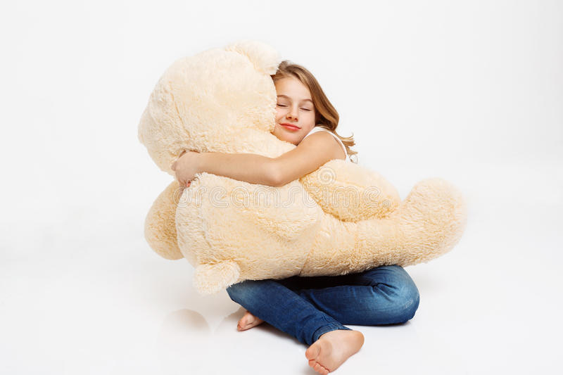 L'enfant gai s'asseyant sur le plancher tenant le jouet concernent des genoux image libre de droits