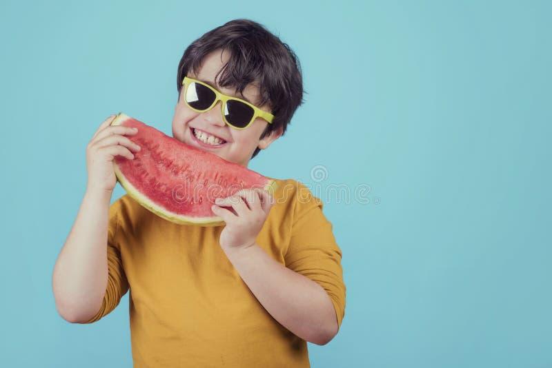 L'enfant heureux avec des lunettes de soleil mange la pastèque images libres de droits