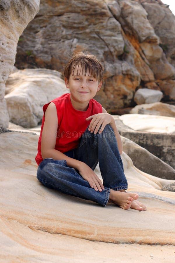 L'enfant heureux détend sur des roches photo libre de droits