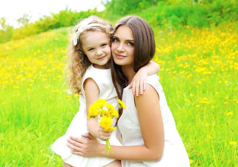 L'enfant heureux de mère et de fille ainsi que le pissenlit jaune fleurit photographie stock libre de droits