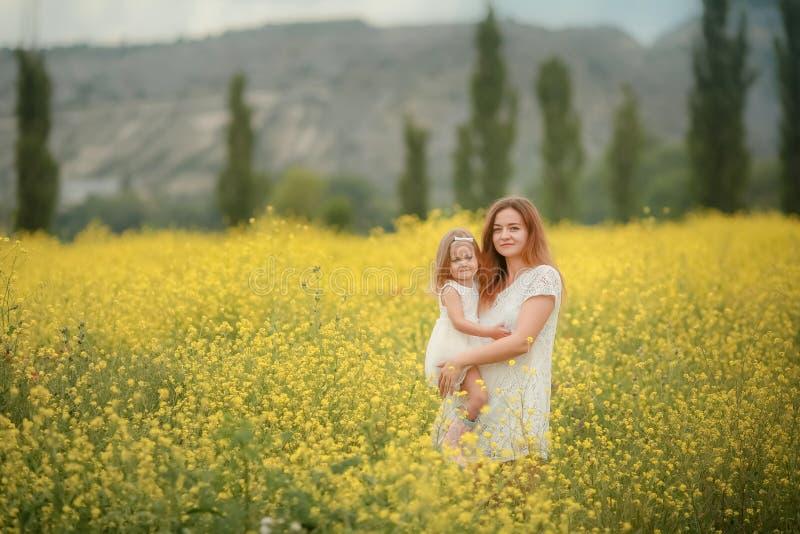 L'enfant heureux de m?re et de fille ainsi que le pissenlit jaune fleurit dans le jour d'?t? images stock