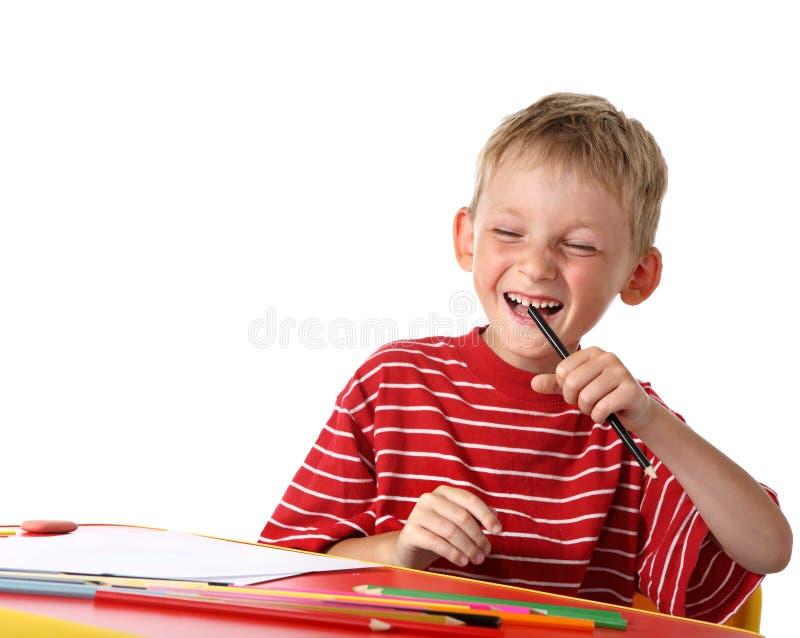 L'enfant heureux dessine avec les crayons colorés image libre de droits