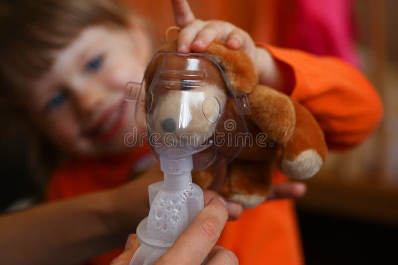L'enfant heureux fait l'inhalation à la maison pour image stock