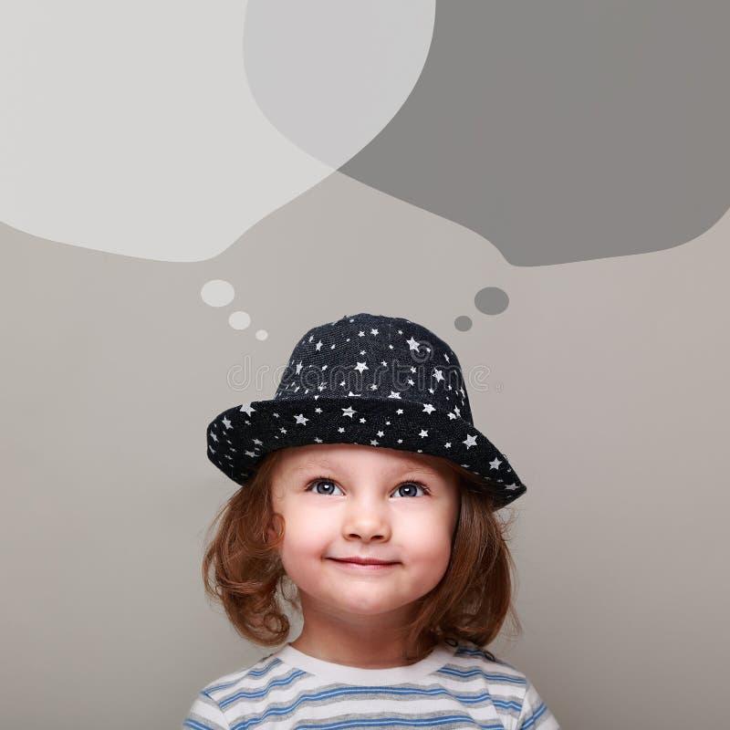 L'enfant heureux imaginant et regardant sur la causerie bouillonne en haut images stock