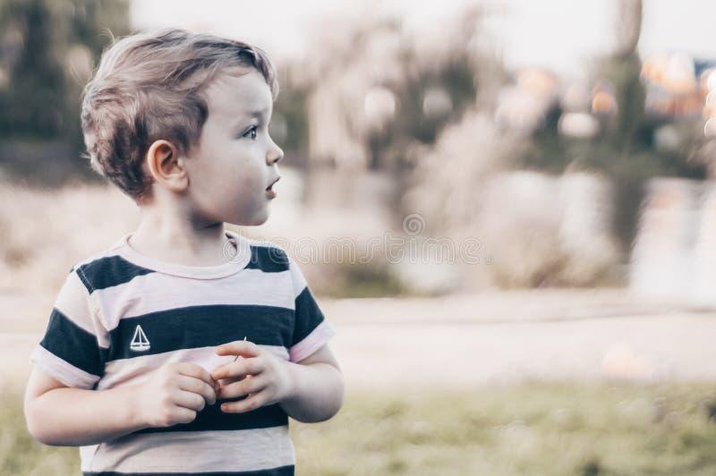 L'enfant heureux, petit garçon regarde vers le bas, regard songeur et tenir dans des mains les croissances dehors L'espace pour l image libre de droits