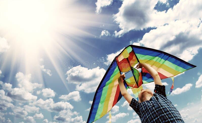 L'enfant heureux pilote un cerf-volant dans le ciel 2 photographie stock libre de droits