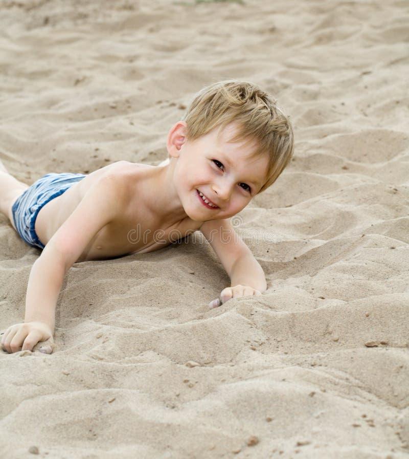 L'enfant heureux s'expose au soleil sur une plage photo stock